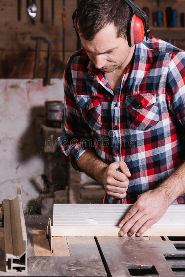 Timmerman die aan een elektrische cirkelzaag werken die sommige raad snijden stock afbeelding