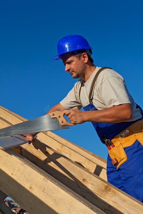 Timmerman die aan het dak werkt stock foto's