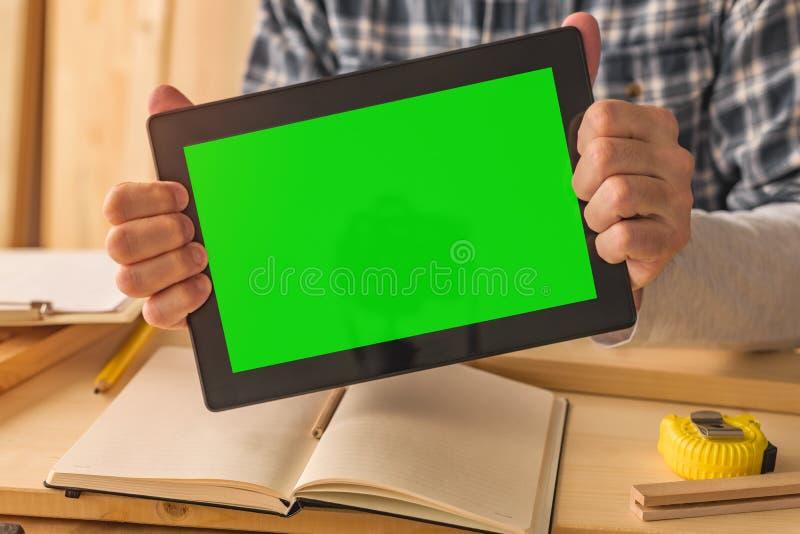 Timmerman die digitale tablet met groene het schermspot houdt op malplaatje stock fotografie