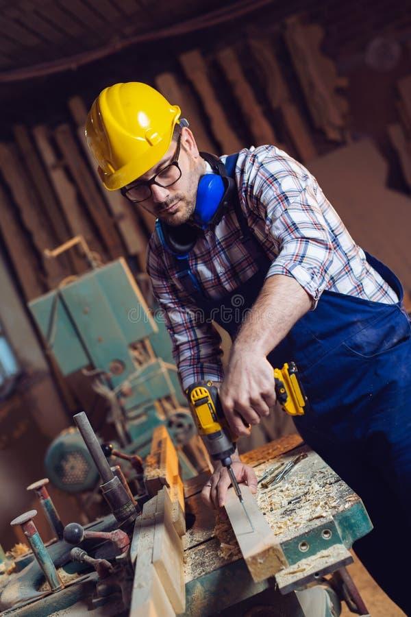 Timmerman die een gat in houten plank op werkbank boren stock fotografie