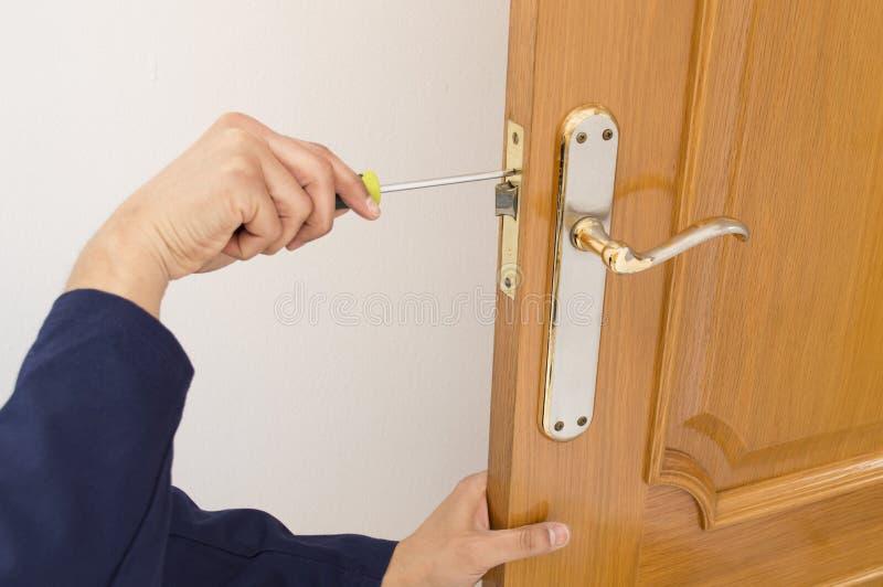 Timmerman die een slot in de deur met een schroevedraaier bevestigen stock foto's