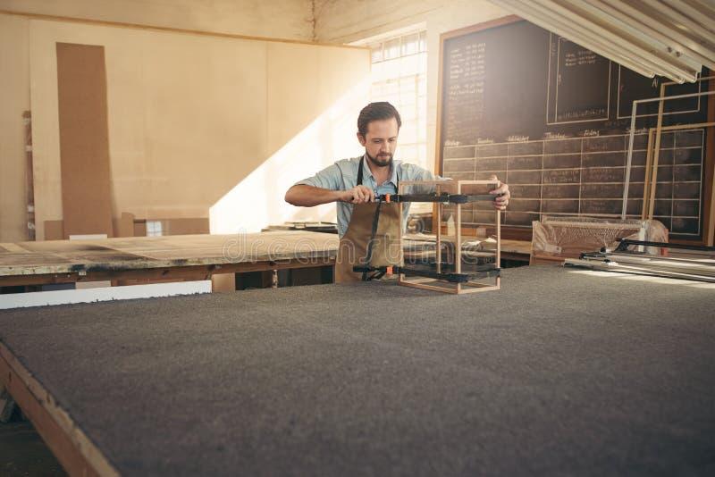 Timmerman die een vitrine in zijn workshop maken stock fotografie