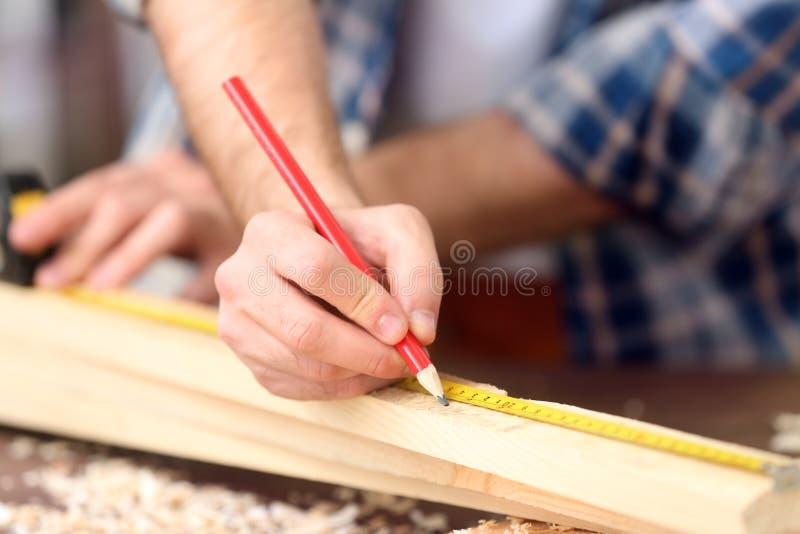 Timmerman die het merken op houten raad toepassen royalty-vrije stock afbeeldingen
