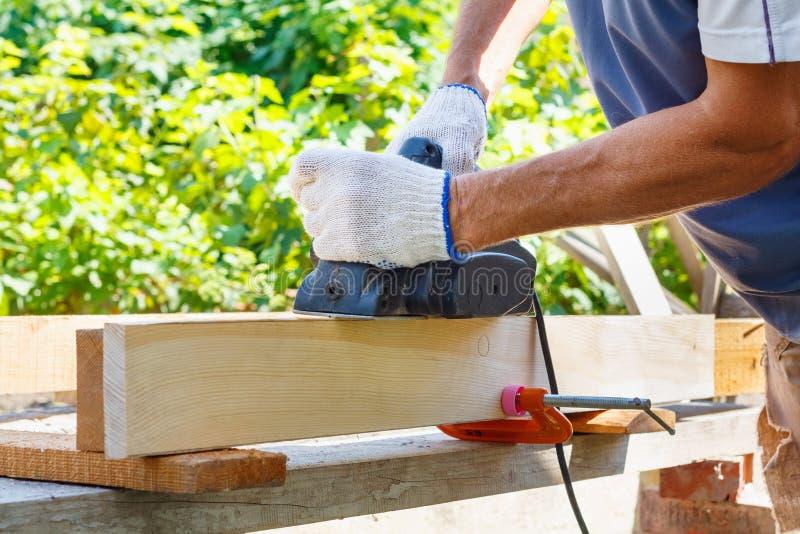 Timmerman die met elektrische planer aan houten plank werken stock foto