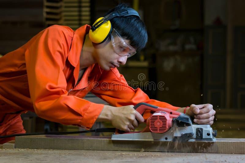 Timmerman die met elektrische planer aan houten plank werken om de oppervlakte in zijn timmerwerkworkshop glad te maken stock fotografie