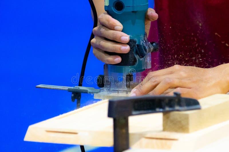 Timmerman die met elektrische planer aan houten plank in worksh werken royalty-vrije stock afbeelding