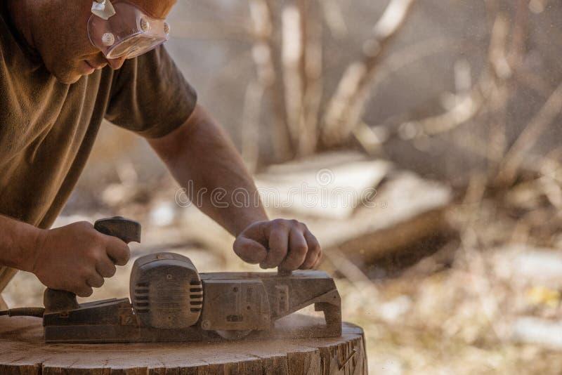 Timmerman die met elektrische planer aan houten stomp in openlucht werken stock foto's