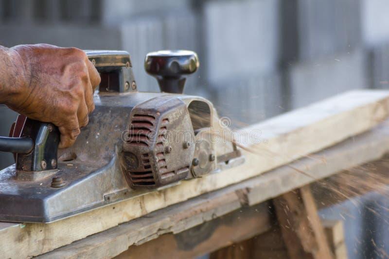 Timmerman die met elektrische planer werkt stock fotografie