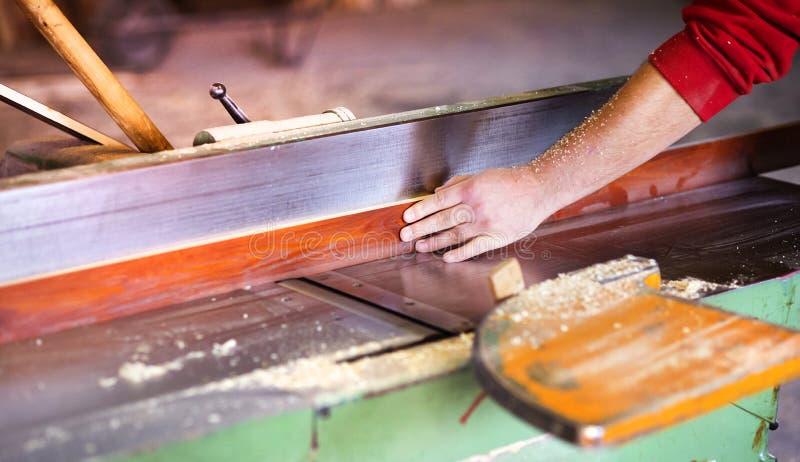 Timmerman die met houten planer werken stock afbeeldingen