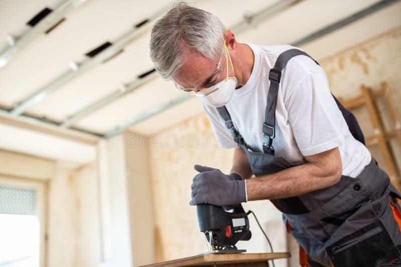 Timmerman die met houten plank op workshop werken royalty-vrije stock foto's