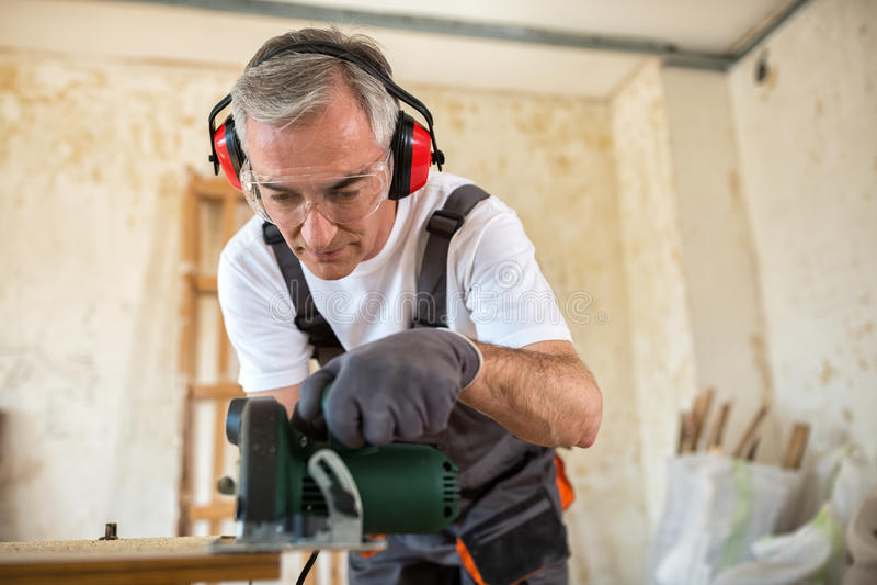 Timmerman die met houten plank op workshop werken stock fotografie