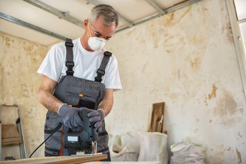 Timmerman die met houten plank op workshop werken stock foto