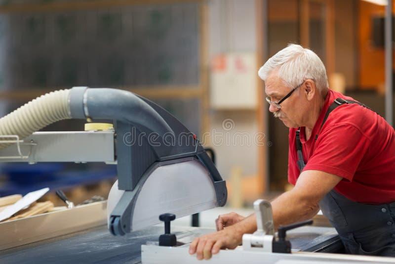 Timmerman die met paneelzaag bij fabriek werken stock afbeelding