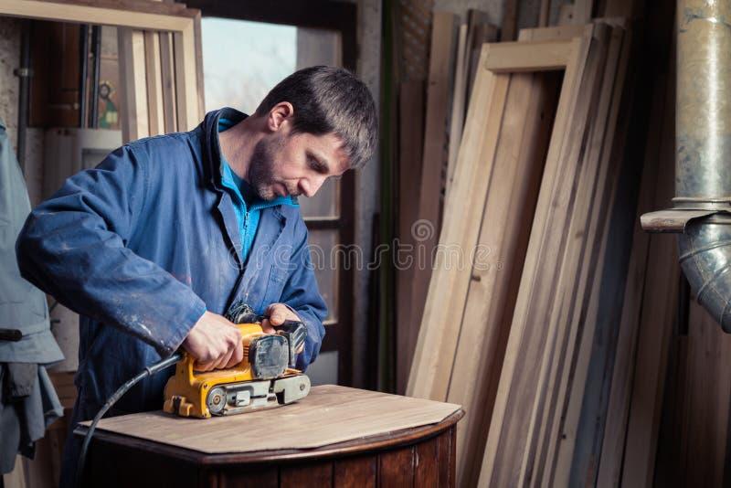 Timmerman die meubilair met riemschuurmachine herstellen stock foto's