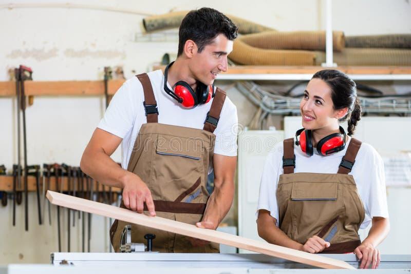 Timmerman en leerling die in workshop samenwerken stock afbeelding