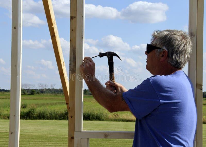 Timmerman het nagelen met een hamer stock fotografie