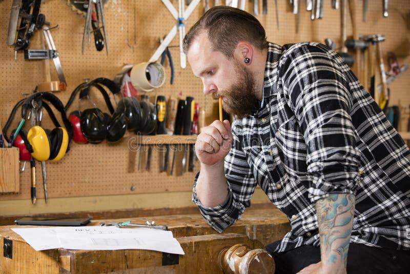 Timmerman het planningswerk en het bekijken tekeningen in de workshop royalty-vrije stock fotografie