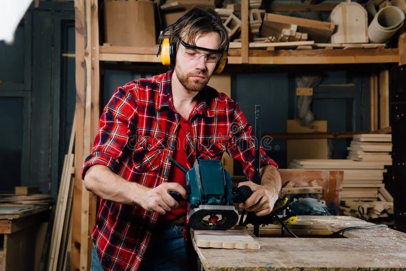 Timmerman het werken van de handmachine van het handmalen in de timmerwerkworkshop schrijnwerker stock afbeeldingen