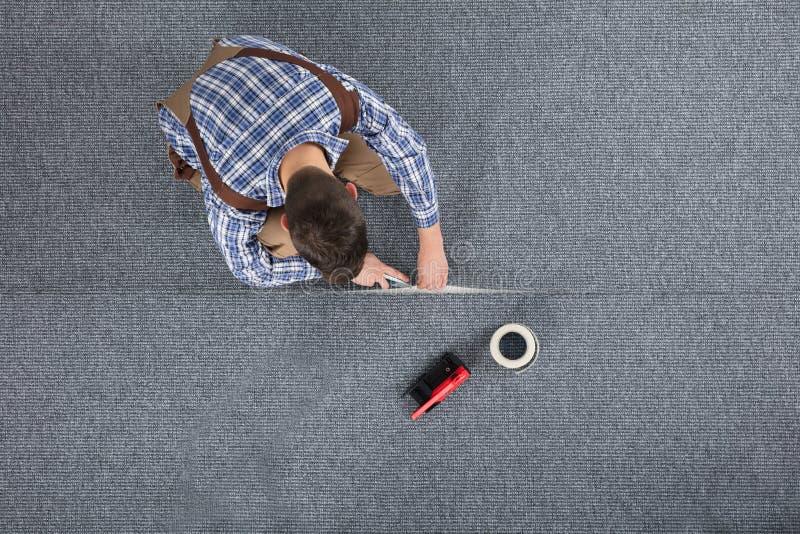 Timmerman Laying Carpet royalty-vrije stock afbeeldingen