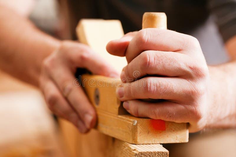 Timmerman met houten planer stock foto