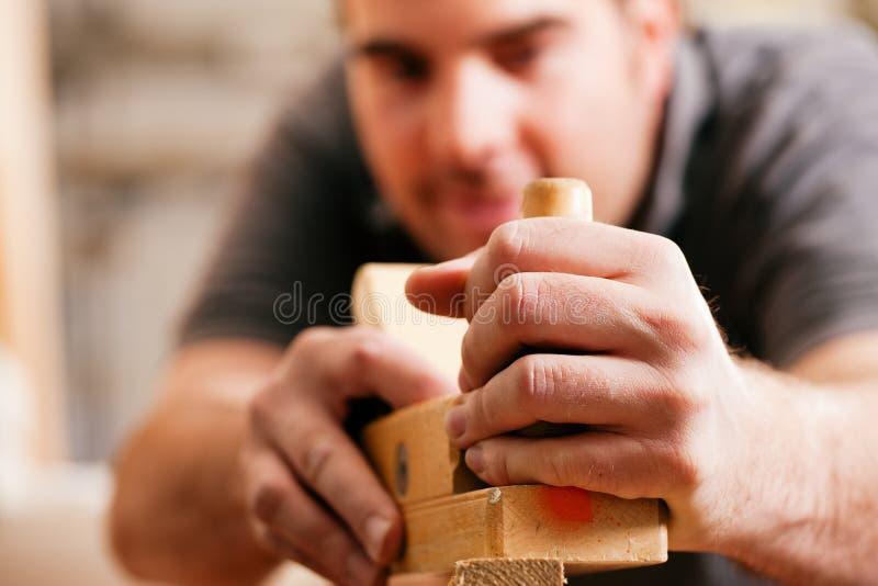 Timmerman met houten planer royalty-vrije stock foto