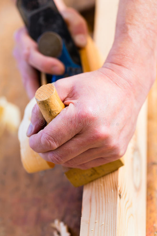 Timmerman met houten planer en werkstuk in timmerwerk royalty-vrije stock foto
