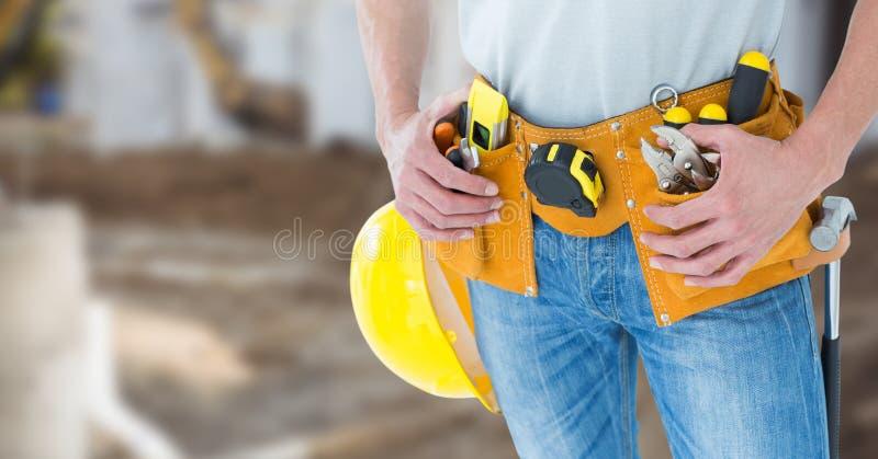 Timmerman met hulpmiddelen op bouwterrein stock foto's
