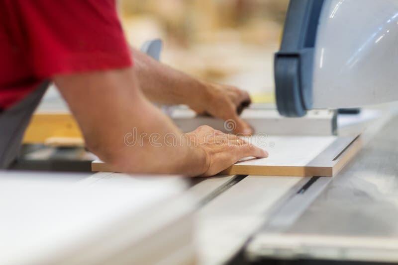 Timmerman met paneelzaag en houtvezelplaat bij fabriek royalty-vrije stock afbeeldingen