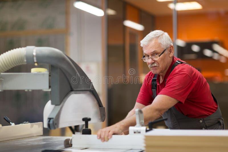 Timmerman met paneelzaag en houtvezelplaat bij fabriek royalty-vrije stock fotografie