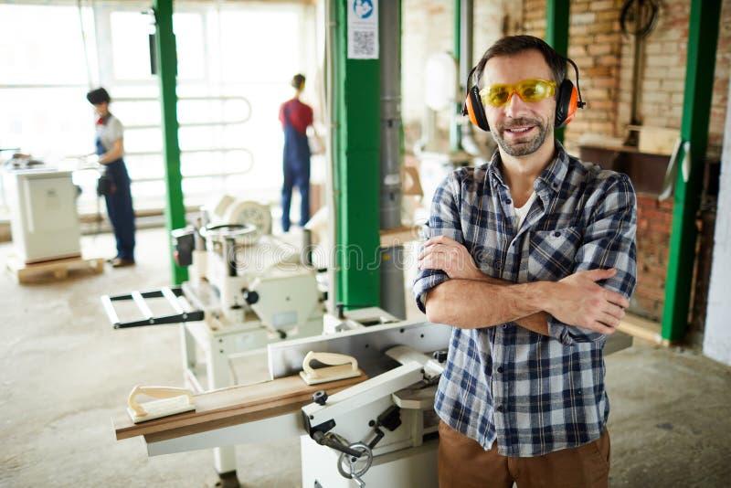 Timmerman in oorbeschermers die zich tegen snijmachine bevinden royalty-vrije stock afbeelding