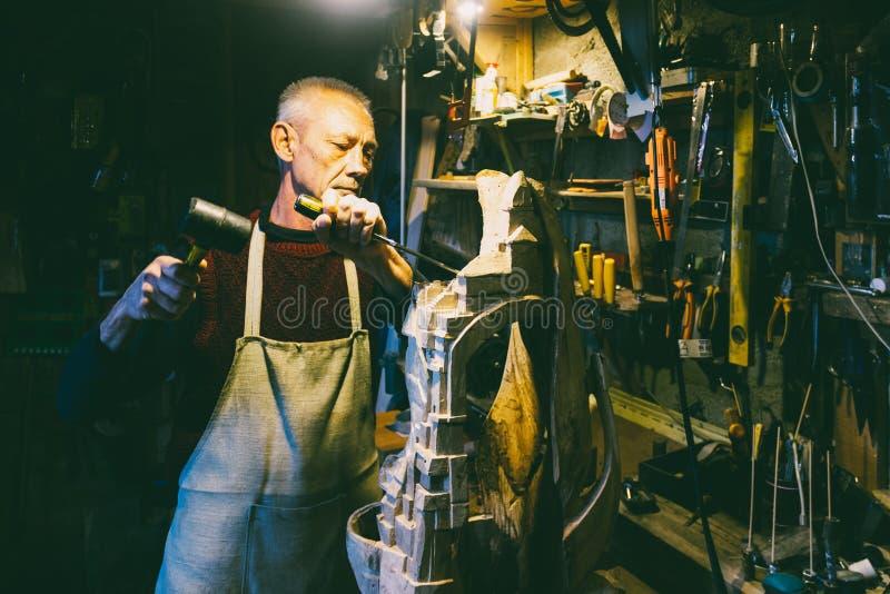 Timmermans 50 - 55 jaar oud creeert houten beeldhouwwerk in de workshop royalty-vrije stock foto
