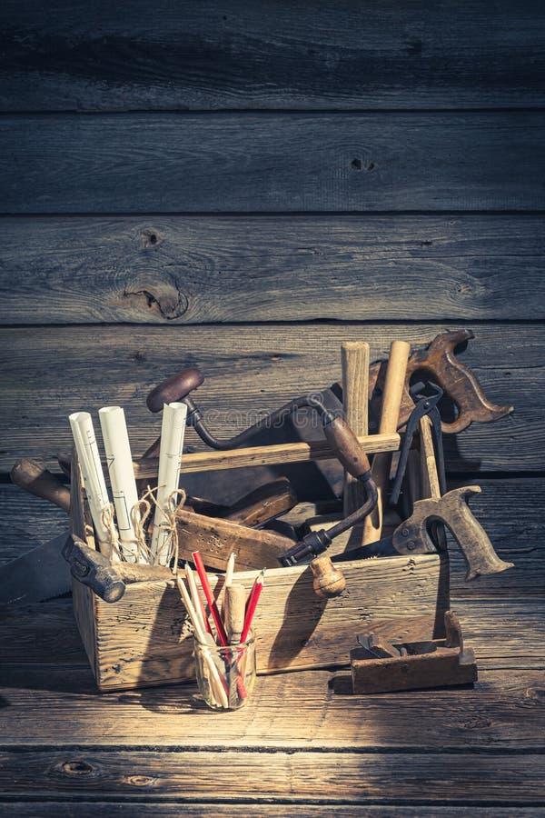 Timmermans werkende hulpmiddelen in een workshop over rustieke houten lijst royalty-vrije stock afbeelding