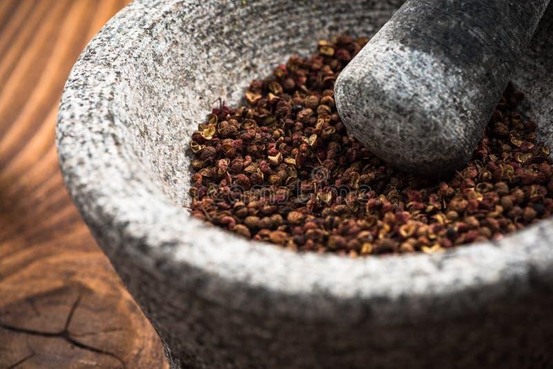 Timut sihuan pepper seeds in granite pestle or mortar.  stock images