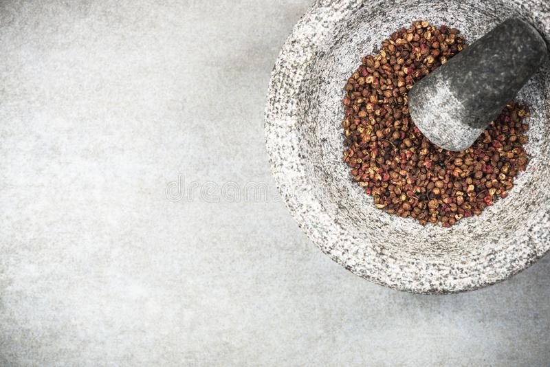 Timut sihuan pepper seeds in granite pestle or mortar royalty free stock photography