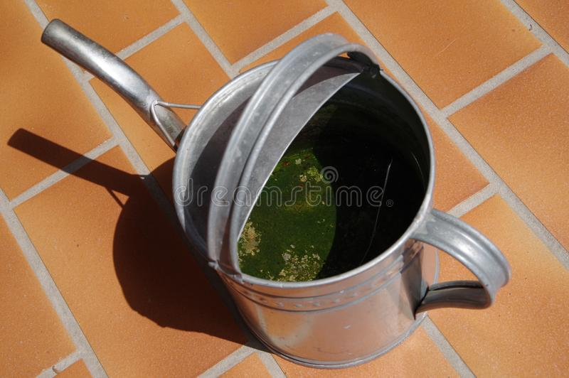 Watering can made of sheet metal on red balcony surface. Tin can with handle, Watering can made of galvanized sheet metal on a red clinker Surface, watering can stock photos