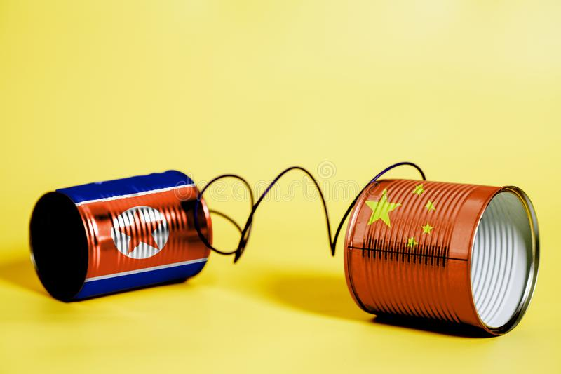 Tin can phone with China and North Korea Flag .communication concept stock photo