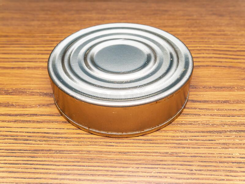 Tin can on a wooden table. Place for text. Background image stock photo