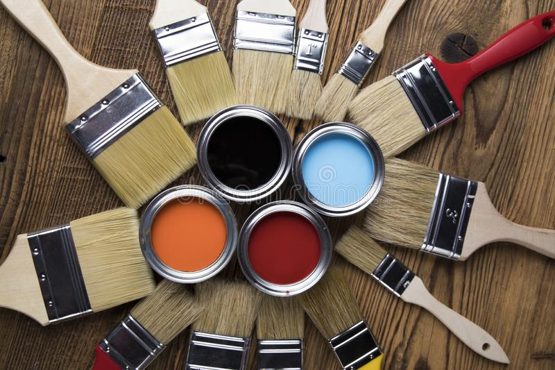 Tin cans with paint, brushes and bright palette of colors royalty free stock photography