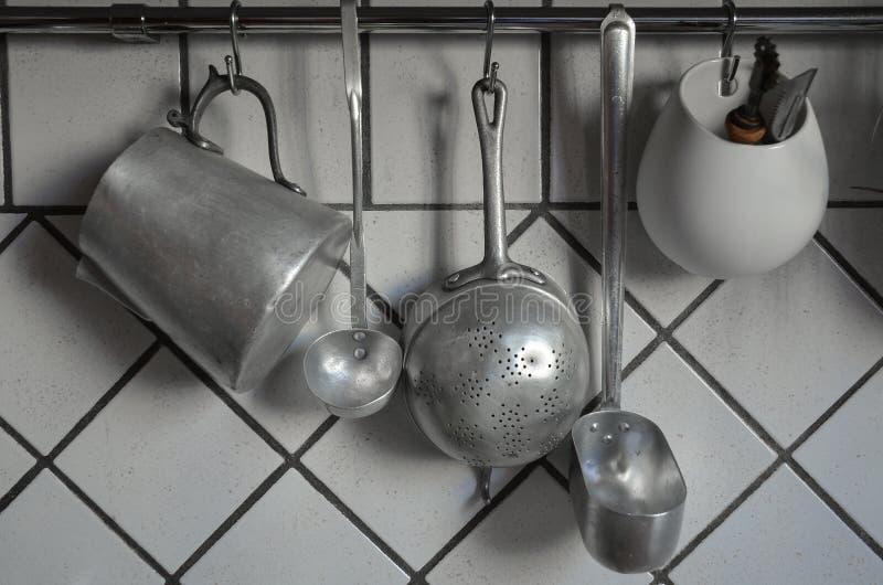Tin coocking utensils hanging in kitchen royalty free stock photo