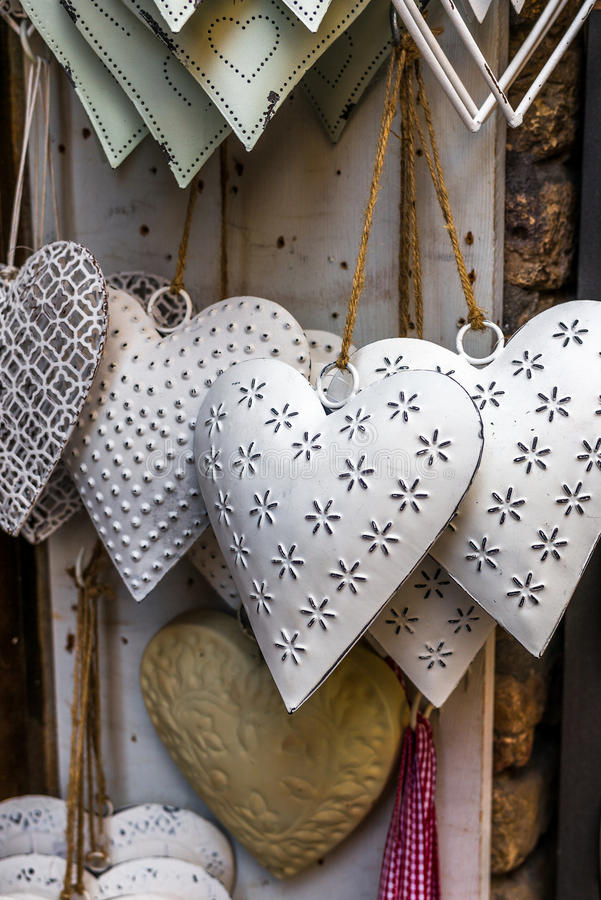 Tin hearts hanging on a window royalty free stock image