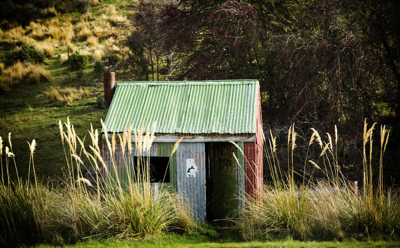 Tin Hut. Small tin hut with open door and grasses nearly as tall as it stock photos