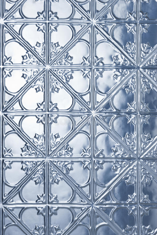 Tin Metal Christmas Winter Background. A pressed or stamped tin metal background with a Christmas snowflake pattern and a cool tone stock photos