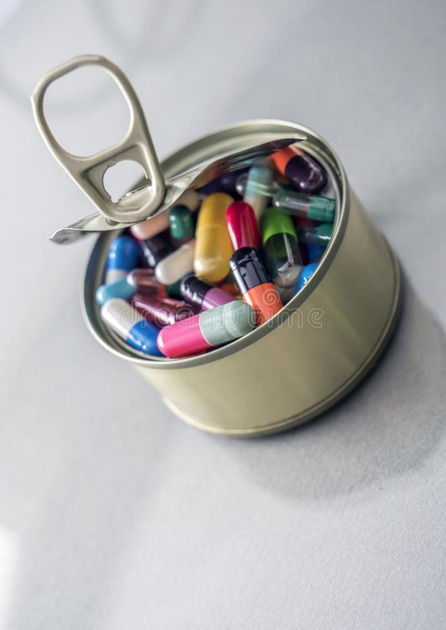 Tin metal contains white pills and red. Conceptual image royalty free stock photography