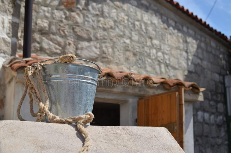 Tin pail and village house. Silver tin pail in front of an old Mediterranean house royalty free stock photography
