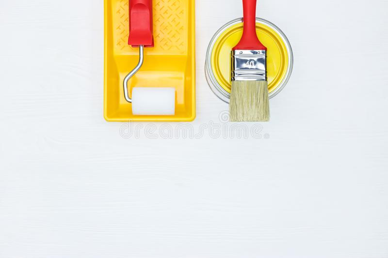 Tin with yellow paint, paintbrush, roller and paint tray on whit. E background flat view stock images