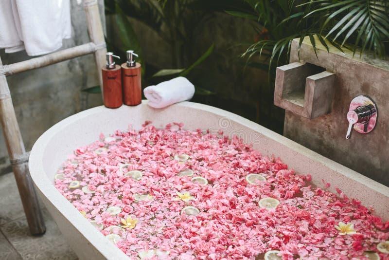 Tina de baño con los pétalos de la flor, la toalla y los productos de belleza imagenes de archivo