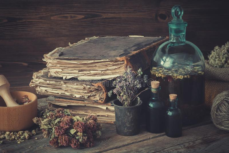 Tincture bottles, assortment of dried healthy herbs, old books, wooden mortar, sack of medicinal herbs. Herbal medicine. stock photos