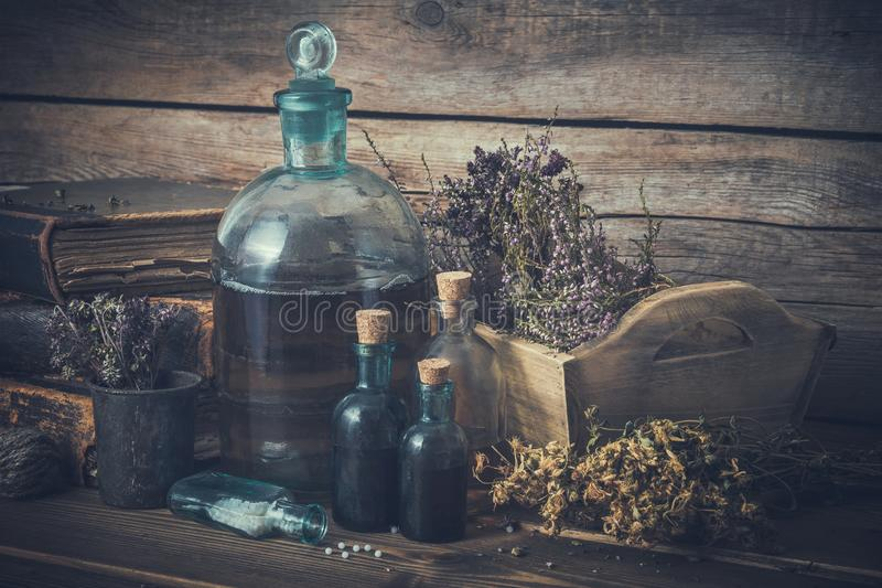 Tincture bottles, vial of homeopathy globules, old books, dry healthy herbs and curative drugs. Herbal and homeopathic medicine. Retro styled royalty free stock photos