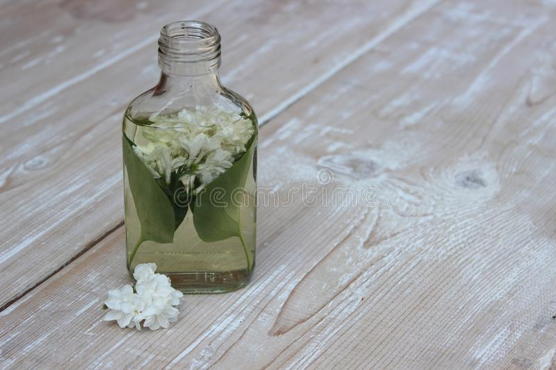 Tincture of lilac flowers. Medical tincture from flowers of white lilac on boards royalty free stock photo