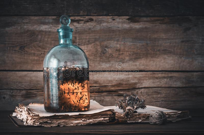 Tincture or potion bottle, old book and bunch of dry healthy herbs. royalty free stock photo